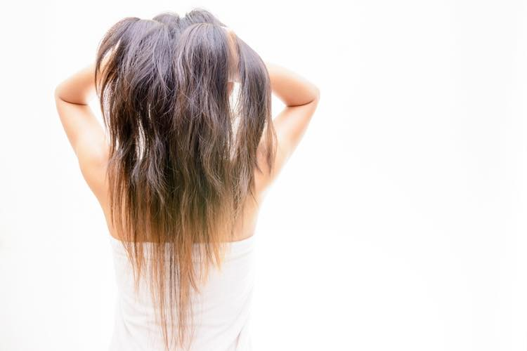 傷んだ髪を気にする女性