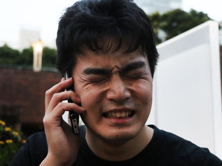 泣きながら電話をする石田