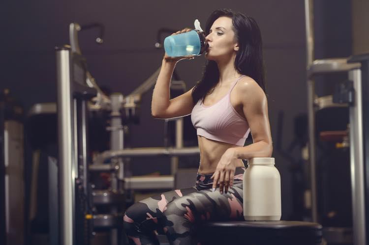 トレーニング時にサプリメントを飲む女性